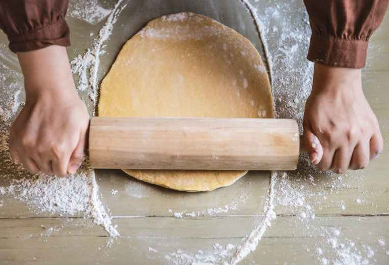 person flattening dough with rolling pin