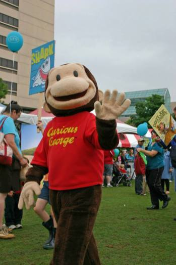 Photo of Curious George leading Parade of Books taken from Knox County Library Facebook page