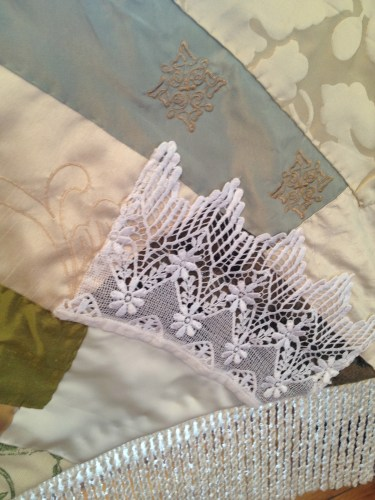 Soft colors and touches of lace in a quilted throw