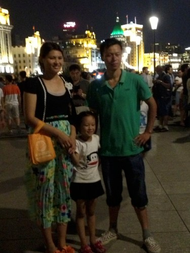 A family willingly posed for a picture standing in front of the illuminated buildings in The Bund.