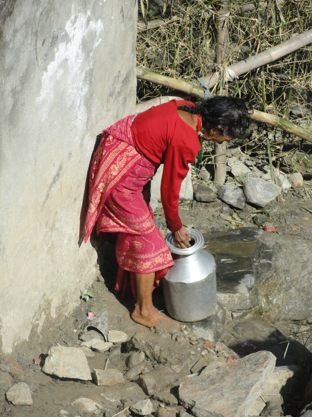 Woman in Nepal filling jug with water