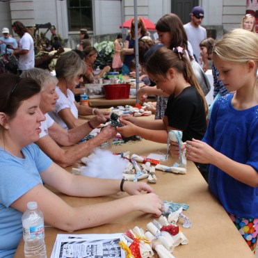 Teaching young girls how to make cloth dolls