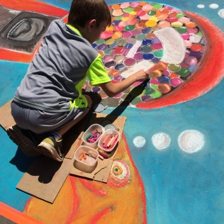 Balancing on cardboard squares, this student from Sequoyah Elementary adds color to their school's Chalk Walk entry.