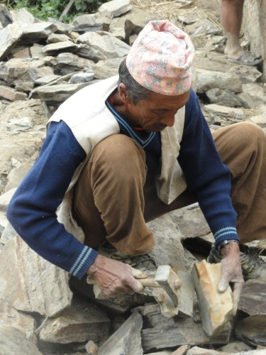 Stone cutter breaks up stone to form building blocks for a new home in Nepal