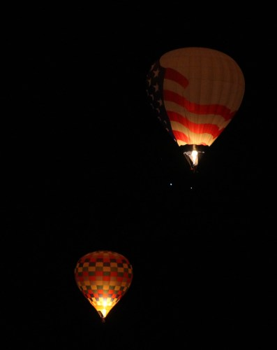 Floating skyward in the darkness, two of the early risers light up the sky.