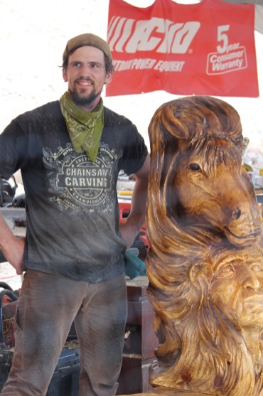 Chainsaw Carver standing by his finished product right before judging.