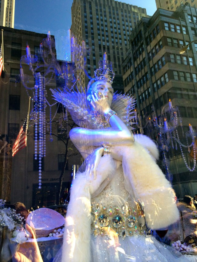 A mannequin in white fur and winter finery poses in the Christmas 2015 windows at Saks with a cityscape reflection in the background.