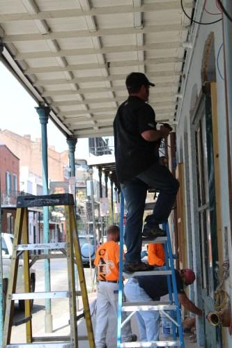 Repairing a door on St. Charles Avenue.
