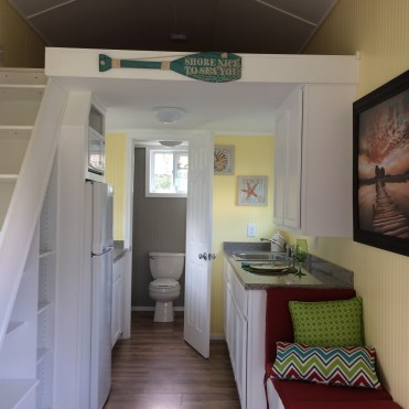 Inside the ground floor of a portable tiny house with a beachy theme. Stairs lead to loft sleeping area.