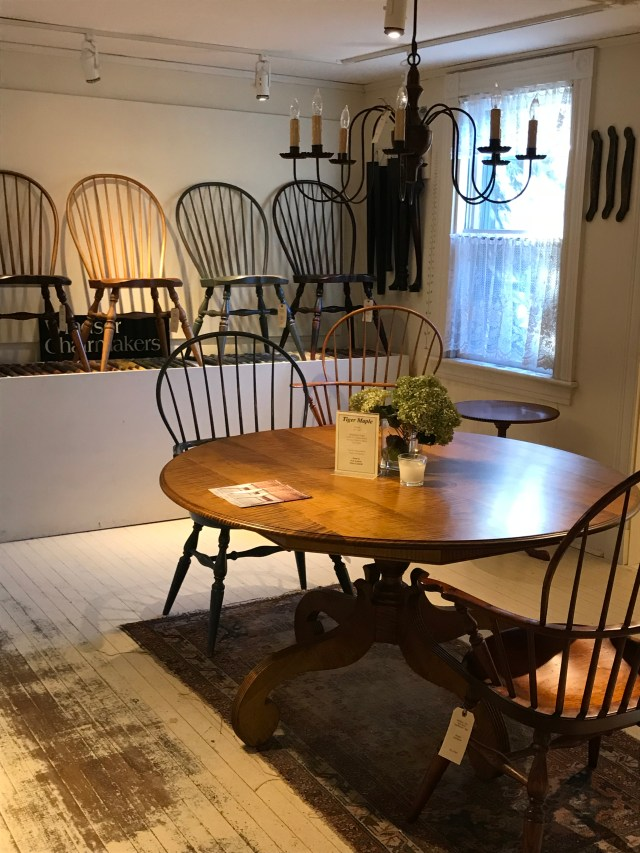 Lined up Windsor chairs in a variety of finishes at Windsor Chairmakers, Lincolnville, ME