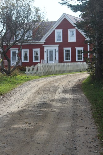 Red cottage with fencing on the path to lighthouse hill.