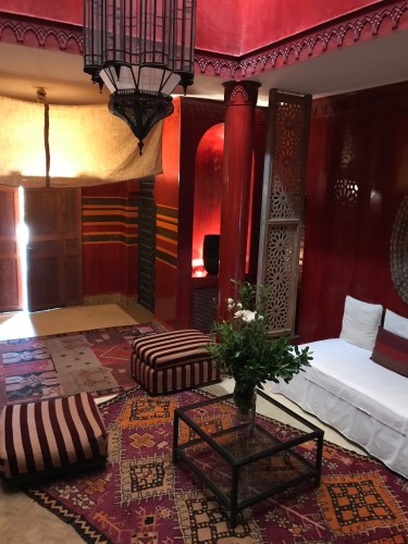 Indoor gathering spot with red patterned accessories: Jnane Tamsna