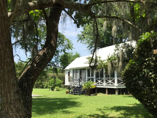 Sweet Southern home in McClellanville, SC complete with front porch, quiet grounds, and trees festooned with Spanish moss.