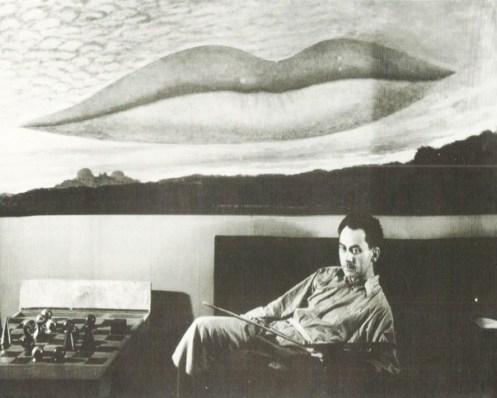 Man Ray with one of his iconic paintings.