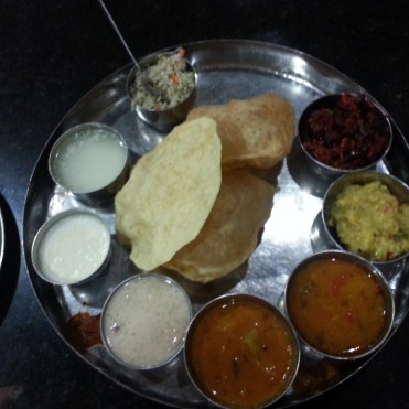 The complete Kannada meal: puris, papad, beetroot palya, puttu (ground rice+grated coconut), rasam, sambar, curd, whey and payasam (dessert)