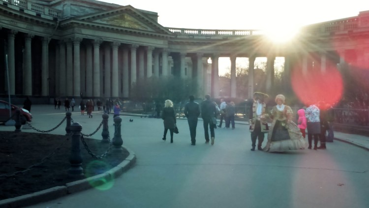 A couple dressed in traditional royal attire glides past the Kazan Cathedral