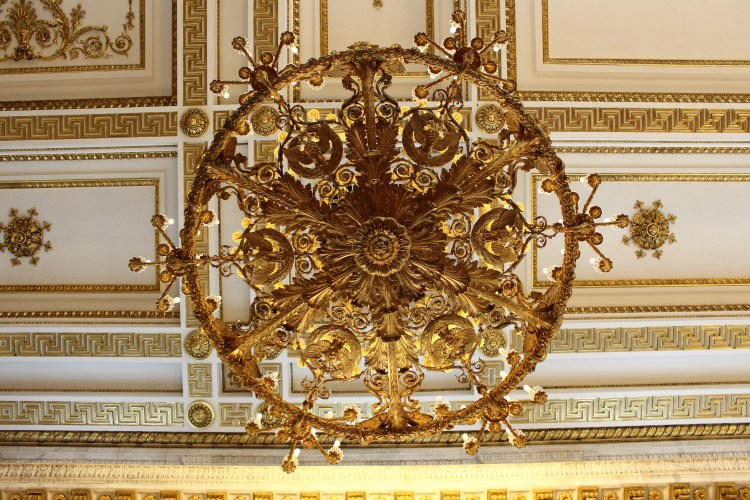 An exquisitely designed chandelier hangs from the ornate ceiling of the Hermitage Museum