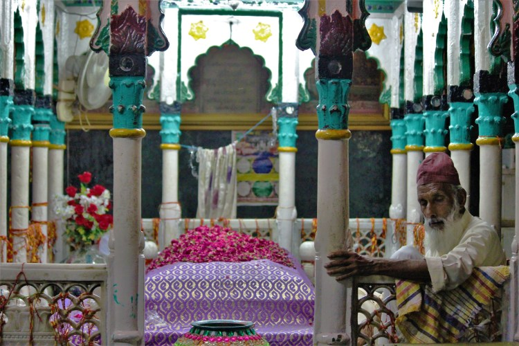 The imam watches over the coffin of Khwaja Qutbuddin Bakhtiyar Kaki at the eponymous Islamic shrine.