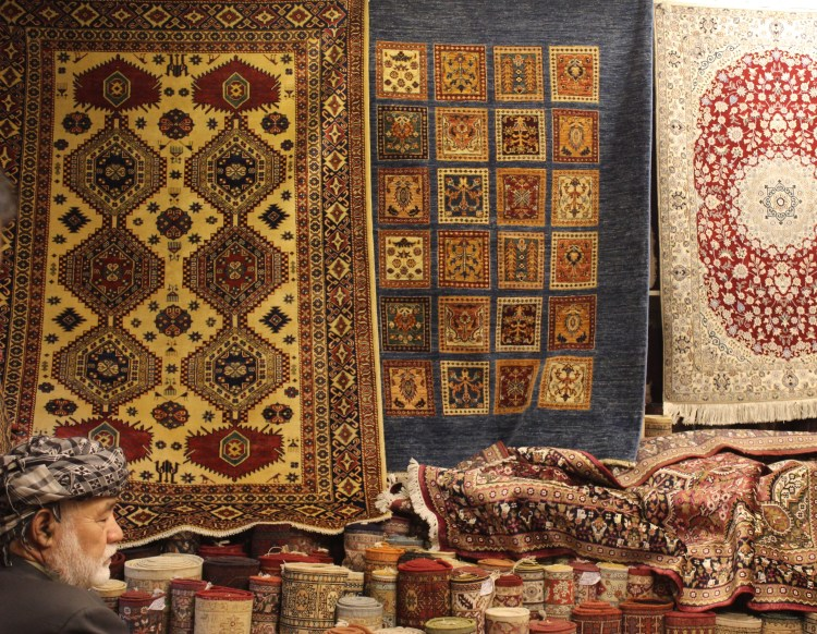 An old Irani trader displays Persian carpets at a souk in Sharjah.