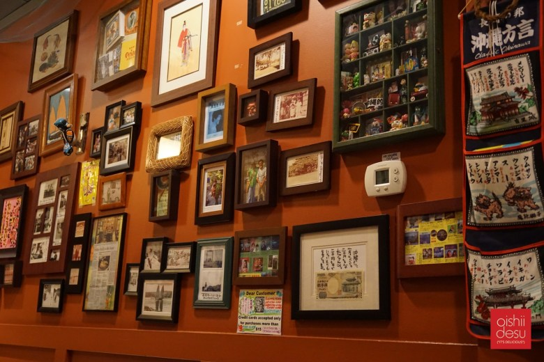 Photo Description: the reddish wall at Habuya in Tustin, CA. The way is filled with tiny frames with a ton of character from pictures, art, to little trinkets.