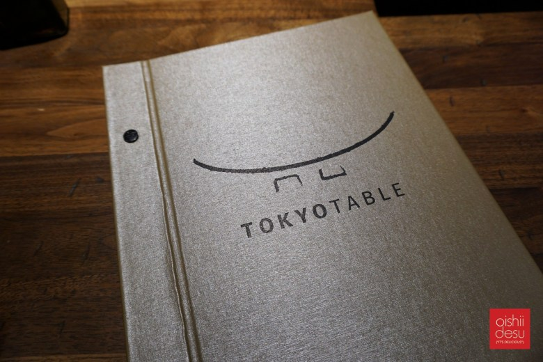 Photo Description: the Tokyo Table menu a top their dark wooden table. The menu is silver, with a thick outer binder that has a course texture to it. In black, the words Tokyo Table are written across it with their logo above it.