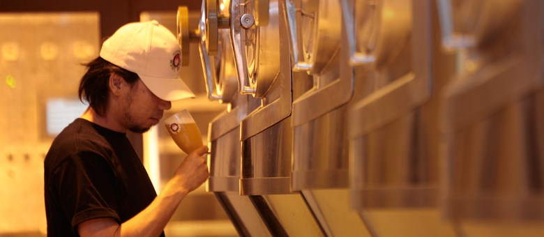 Photo Description: a Hitachino brewer is sniffing a poured glass of beer from one of the several large vats of beer.