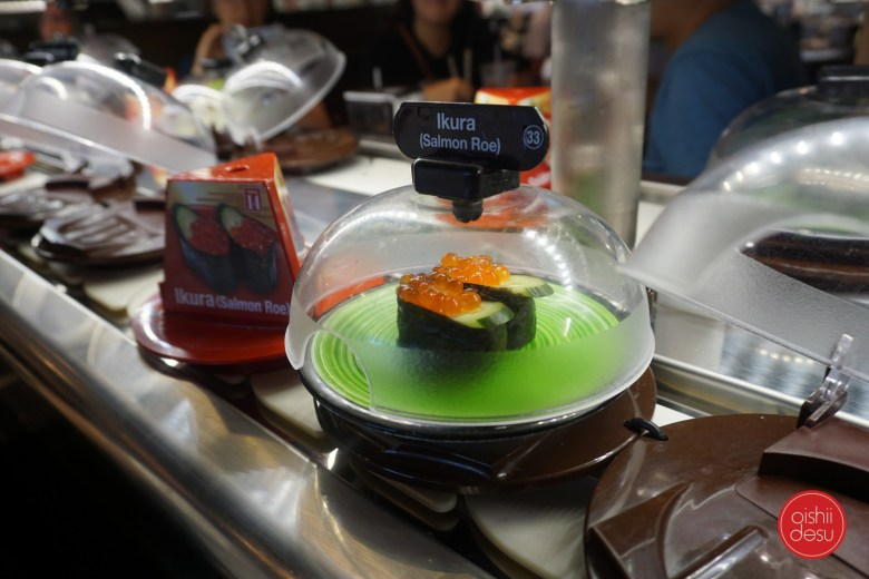 Photo Description: a picture of a kaiten sushi spot that uses conveyor belts to deliver and market their products. On top of the conveyor belt are plates with clear bubble covers to protect the sushi from passerby's. In the picture is Ikura (Salmon Roe).