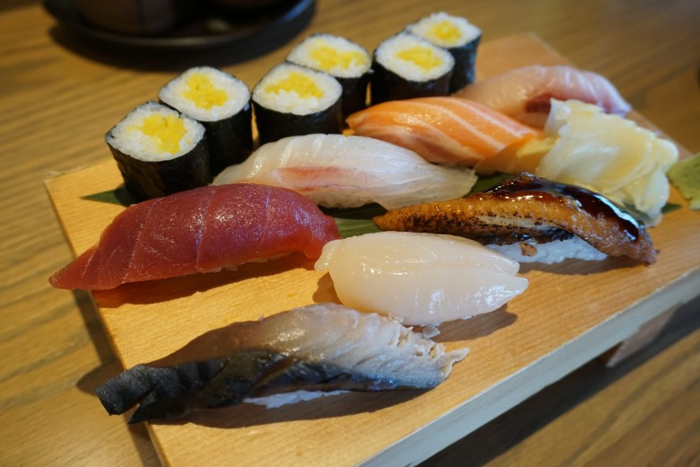 Photo Description: a wooden block plate has a number of pieces of Japanese nigir sushi which is small ovals of sushi rice, with thinly cut pieces of various kinds of raw fish from mackerel, tuna, salmon, scallops, to eel. In the back of the plate is hosomaki which is takuan or pickled vegetables.