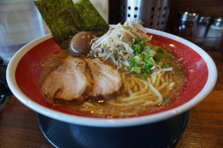 Photo Description: a red an white bowl atop a black plate. Inside the bowl is a soup, ramen noodles, 2 large and thick slices of pork, ajitama (egg), bean sprouts, nori, to green onions.