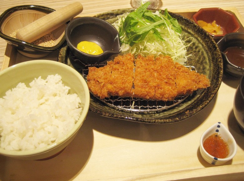 Photo Description: this is the typical spread of a tonkatsu meal which involves 7 different bowls and cups. One is a plate of tonkatsu atop a grated silver plate to make sure it keeps the tonkatsu crispy, karashi mustard, shredded cabbage, fresh sesame seeds in a mortar and pestle, along with sauces for the salad and tonkatsu sauce.