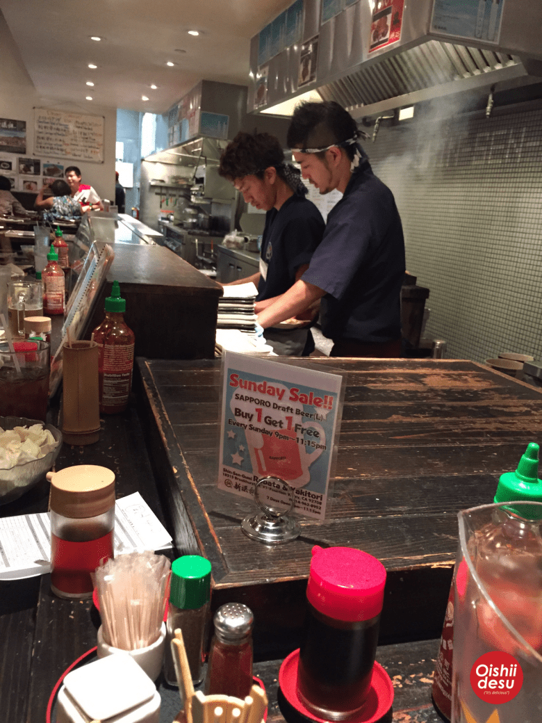 Photo Description: two of the yakitori chefs at Shin Sen Gumi, the two chefs are wearing dark blue shirts, with blue and white headbands tied around their head. The back tile is small square tiles with the words Shin-Sen-Gumi written out.