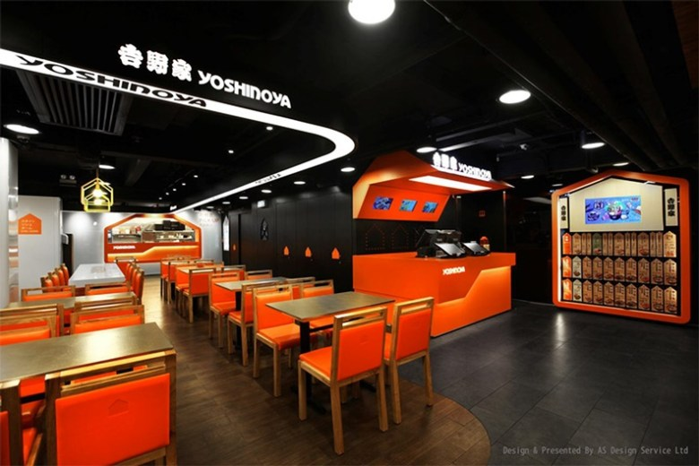 Photo Description: Yoshinoya in Hong Kong designed by AS-Design. This interior is cool AF because it's a dark black balls contrasted with white walls are accented by orange accents from the chairs, front desk, to the opening of the kitchen.