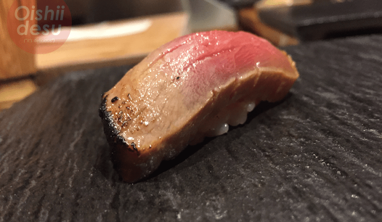Photo Description: a chu toro nigiri sushi. The neta is marinated (zuke) and finished with a light torching on one end.