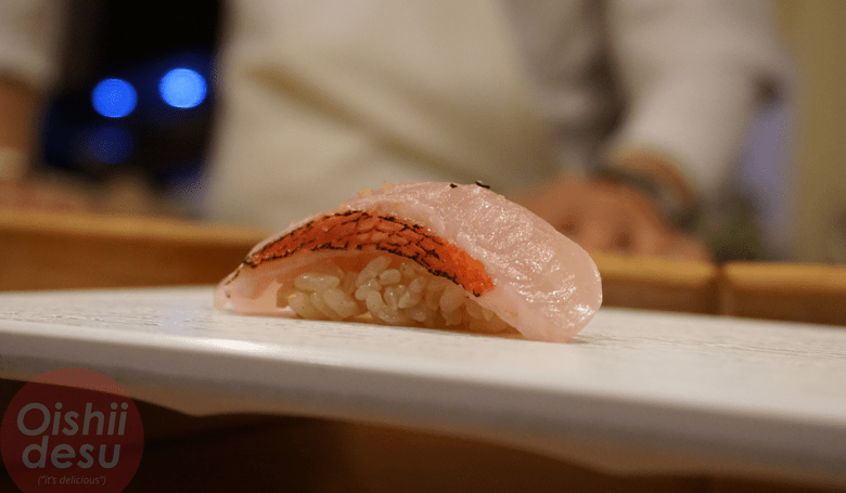 Photo Description: a shot of tai or red snapper nigiri sushi. This shot was taken at Shunji sushi in West Los Angeles. The shot illustrates how the sushi shari su (vinegar mixture) is on the darker red side because the rice almost looks brown.