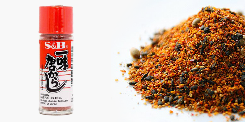 "Photo Description: there is a pile of seeds and bits of chili pepper in a pile atop a white table. On the left is a small bottle of shichimi togarashi which is a clear bottle, red top, with Japanese kana on the front with the romaji ""S&B"" and ""S&B foods, inc, and product of Japan also printed on the label"""