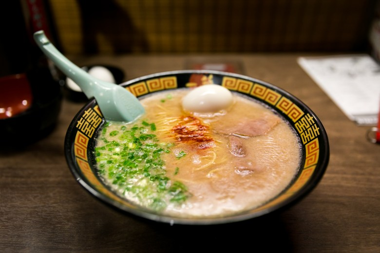 Photo Description: this is a picture of the infamous Hakata ramen by Ichiran. The bowls toppings are very minimal and they include chashu, egg, green onion, and their red chili.