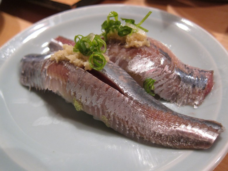 Photo Description: iwashi or sardine sushi is so damn good. Its very visually discernible due the darkish reddish hue with a shiny silver sheen. Grated ginger and sliced green onions top it all off.