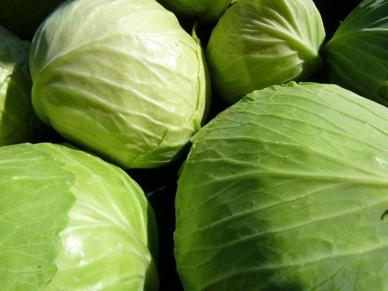 Photo Description: several heads of whole cabbage.
