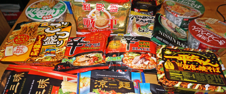 instant-noodles-featured-image. Photo Description: a pile of instant noodles piled atop a table. The bulk of the brands are Japanese, but there is one Korean brand. The packaging is very colorful from black/ed, gold/red, blue, to yellow packaging with Japanese kana.