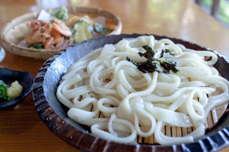 Photo Description: three plates on top of a tablea dark stone looking bowl with a bamboo bottom holds a pile of thick white noodles (udon) with a tiny bit of seaweed on top. in the background the 2nd bowl is blurry due to bokeh and the 3rd bowl, the tiniest most likely has green onion, and ginger in it for the dipping sauce.