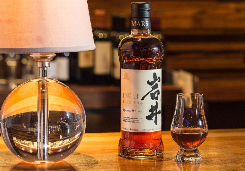 Photo Description: Mars Shinshu whisky has a bottle of their Iwai Tradition whisky (a full bottle), a dram poured neat, next to a lamp that has a glass looking round base with a white contemporary looking lamp shade. Even with the bokeh, you can see several bottles of whisky in the background.