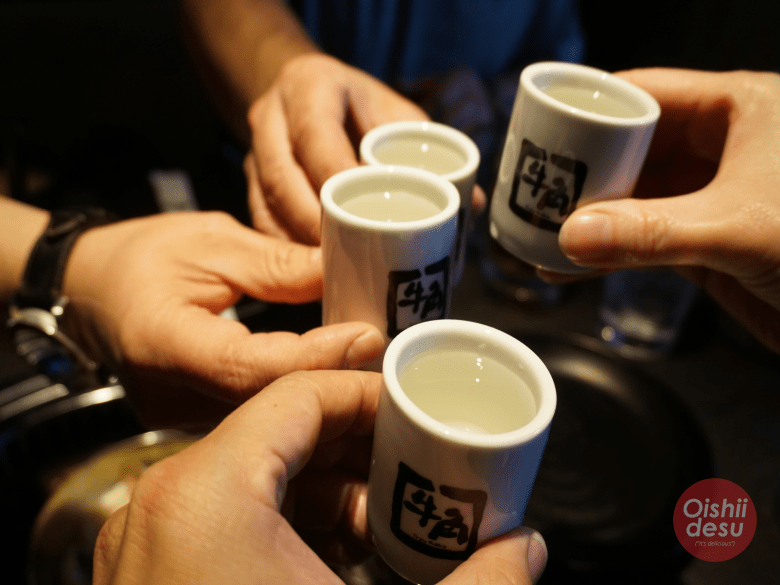 Photo description: 4 sake glasses, with 4 hands holding each glass in a toast (kanpai)