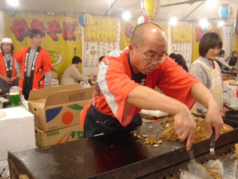 Photo Description: It looks like another festival with a Japanese guy with two metal spatulas mixing up some yakisoba on a teppan (grill).