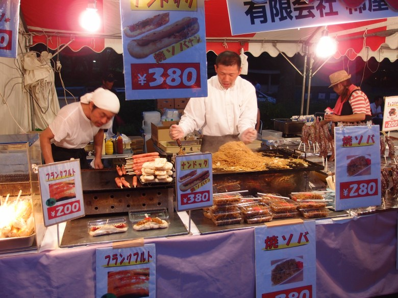 Photo Description: a yakisoba stand at a festival in Japan. They have several products on display for sale with a two guys manning the booth. One is on the teppanyaki with a mound of yakisoba, and the other guy looking over the kushiyaki.