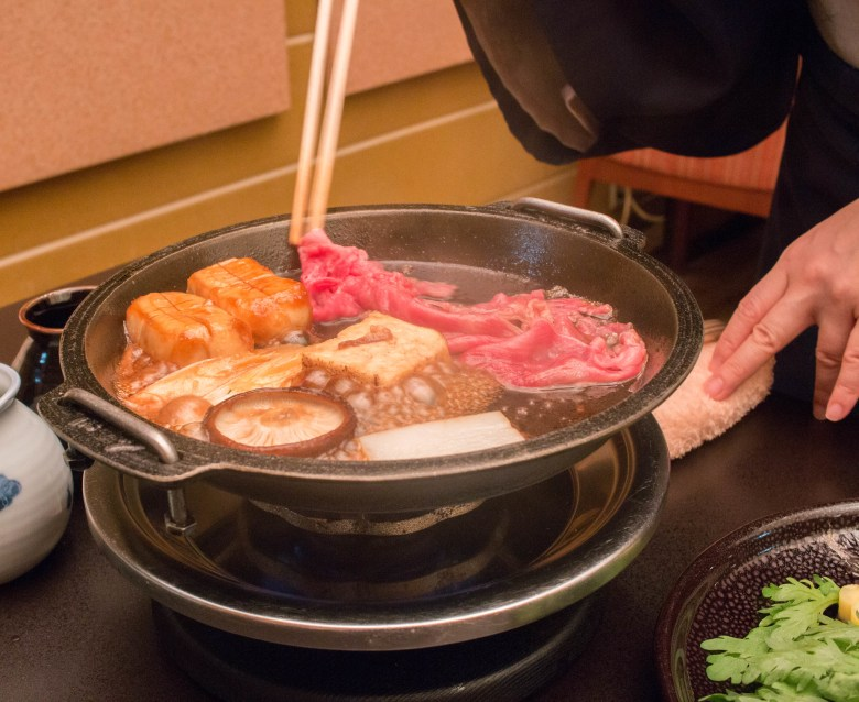 Photo Description: a cast iron pot with sukiyaki in it. The rare meat being placed into it, along with tofu and shiitake.
