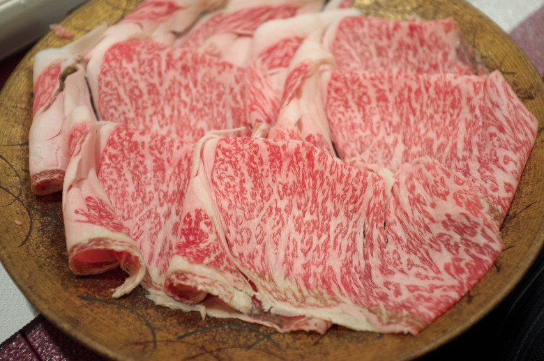 Photo Description: thin strips of wagyu (shinofuri) prepared for shabu shabu. The thin cuts are sitting on a brownish round plate.