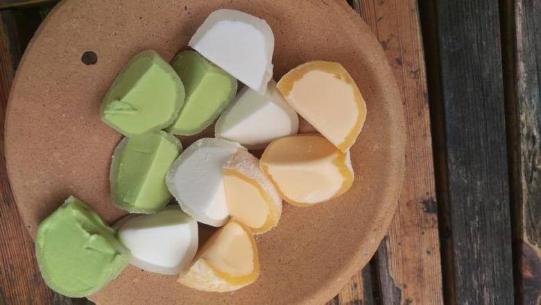 Photo Description: a plate with a number of mochi ice cream cut in half. One of them appears to be green tea, with a peach colored and a white one appear in the image.