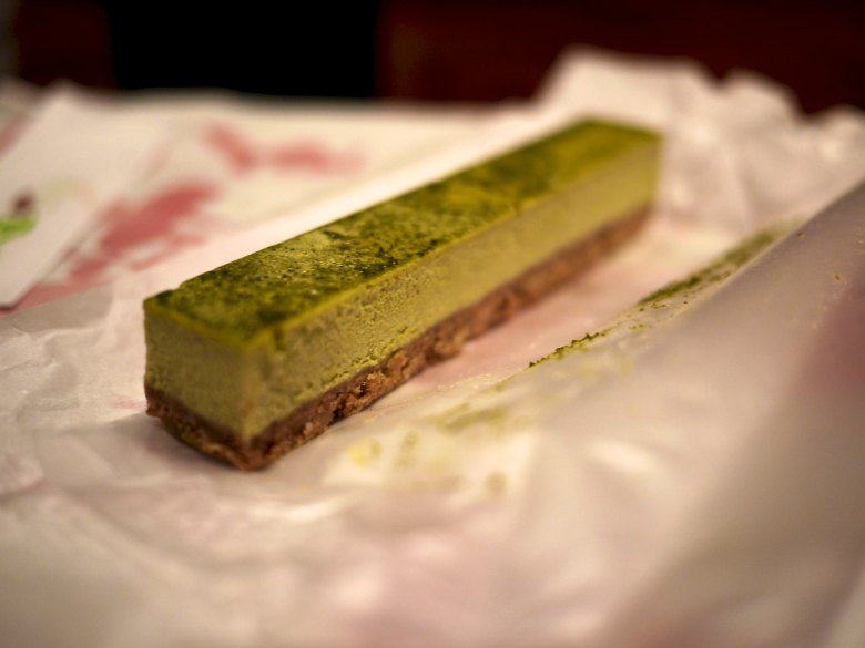 Pictured is a slice of cheesecake in the shape of a 2x2 with sprinkled matcha on it (lots of bokeh in the shot).