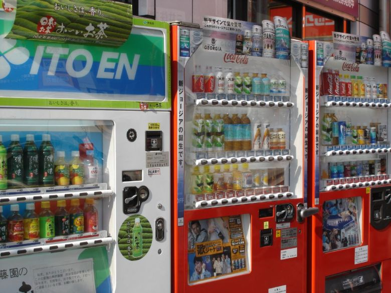 Photo Description: a row of vending machines in Japan. The first one has the ITO EN logo prominently atop the first machine. The other two red ones are filled with various drinks.