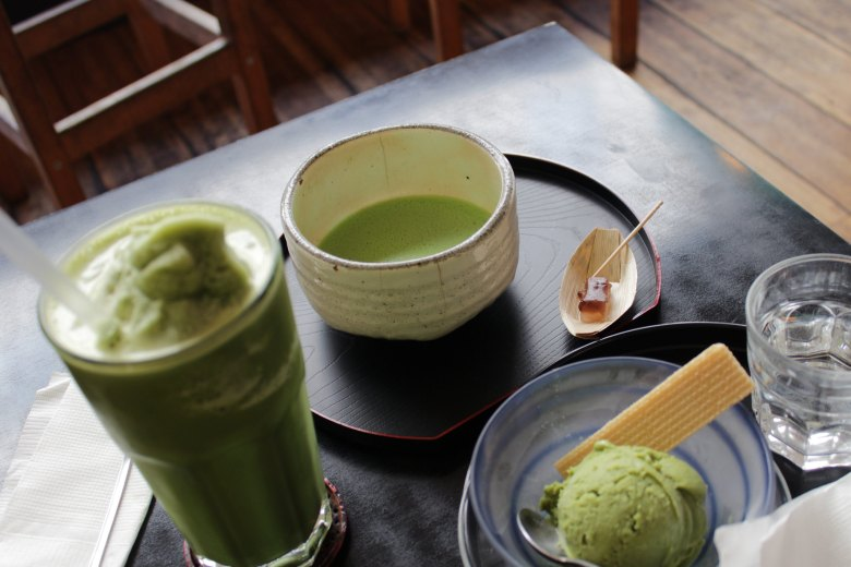 Pictured is of a table shot from above of matcha tea, matcha ice cream, and a matcha latte.